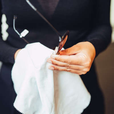 BELLEVUE Mitarbeiterin mit großem Mikrofasertuch in den Händen beim Putzen einer Brillenfassung