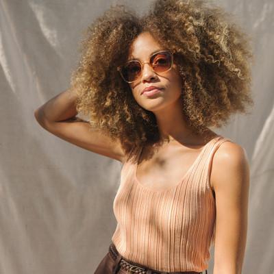 Frauenportrait mit hellbrauner Sonnenbrille und braunen Locken im Afro-Look