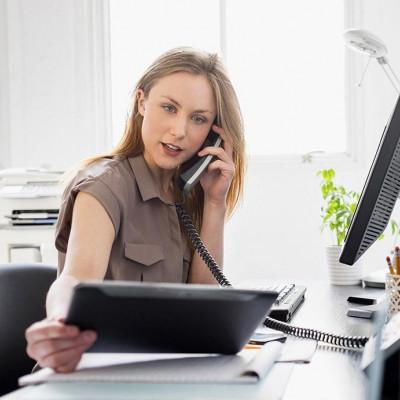 Junge Frau im Büro, gleichzeitig mit Bildschirm, Tablett und Telefon hantierend.