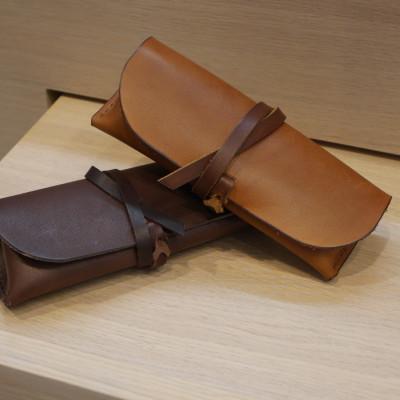 2 edle Leder-Brillenetuis aus Leder mit Band zum Umwickeln und Verschließen in hell- und dunkelbraun.