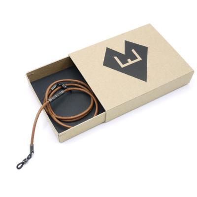 Hellbraune Leder-Brillenkette aufgerollt in einer kleinen Pappbox mit dem Logo von von Ernst.