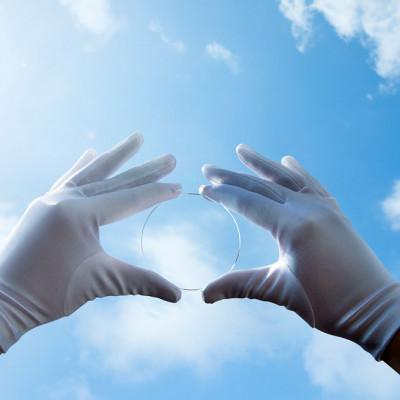 Fast unsichtbares Brillenglas, gehalten von 2 Händen in weißen Handschuhen vor blauem Himmel mit Wölkchen.